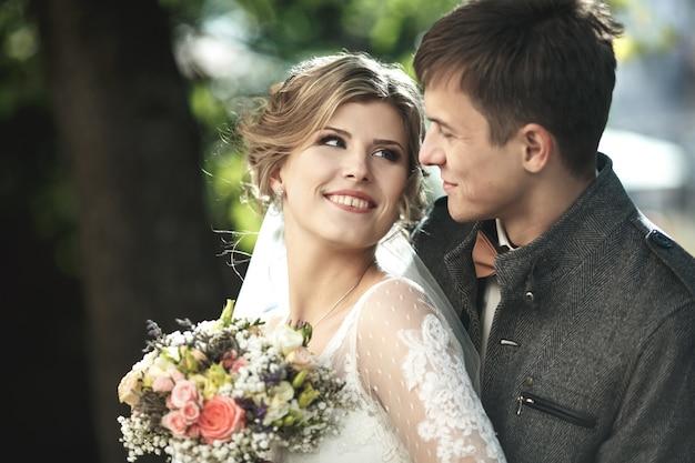 Noivo abraçando por trás de sua namorada com o vestido