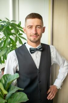 Noivo alegre de terno e gravata borboleta retrato interior