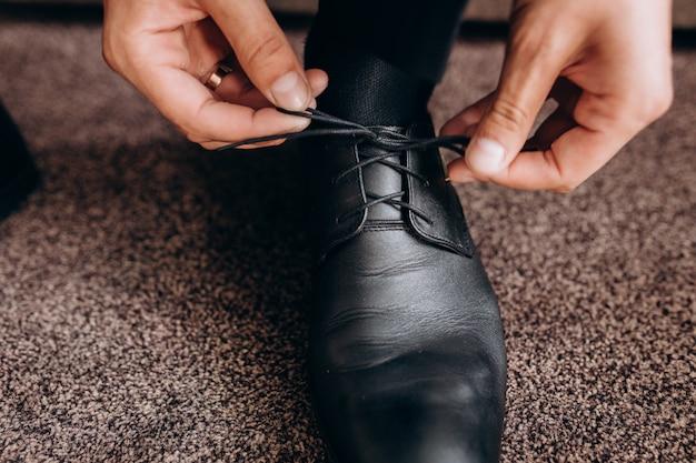 Noivo amarra cadarços nos sapatos, sentado em um sofá