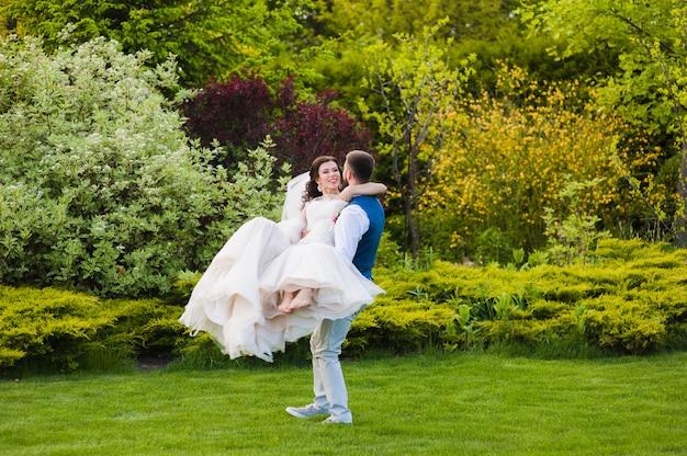Noivo apaixonado turbilhão sua noiva descalça sorridente