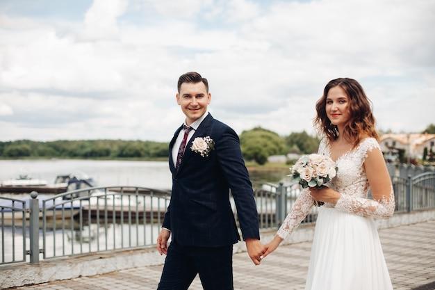 Noivo atraente em um terno preto com sua linda noiva em um vestido longo branco perto do lago