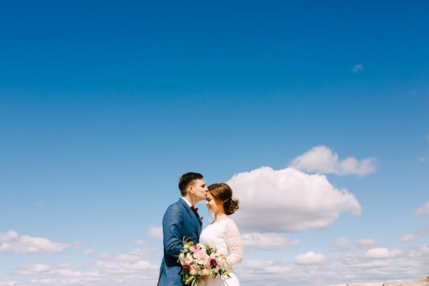 Noivo beija a noiva na testa contra o céu azul brilhante. noiva segura um buquê