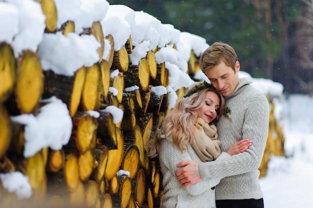 Noivo beija a noiva no templo. recém-casados com buquê senta-se na neve no fundo de madeira. casamento de inverno