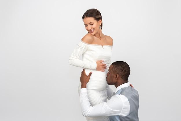 Noivo beijando a barriga da noiva grávida