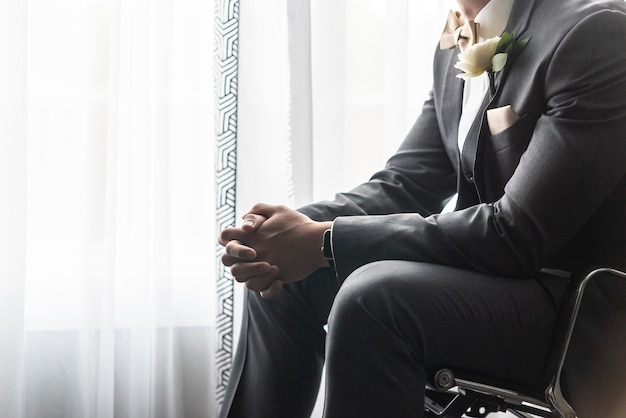 Noivo bonito de terno preto rezando antes da cerimônia de casamento