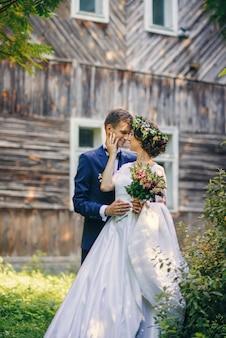 Noivo bonito e noiva encantadora pechinchando ternamente perto da antiga casa de madeira no parque