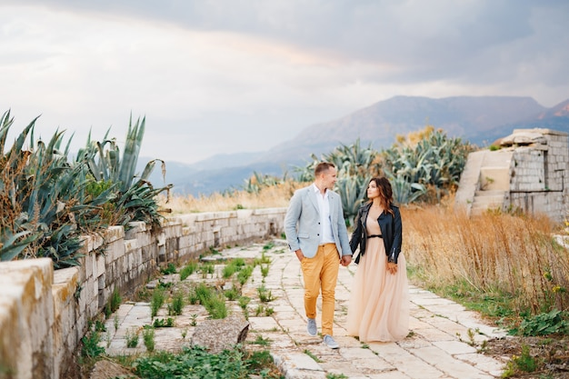 Noivo bonito em um terno brilhante e a noiva em uma jaqueta de couro caminham de mãos dadas pelas ruínas de