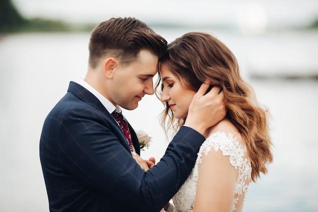 Noivo bonito em um terno preto com uma linda noiva em um vestido longo branco no parque fica perto do lago