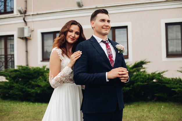 Noivo bonito em um terno preto com uma linda noiva em um vestido longo branco