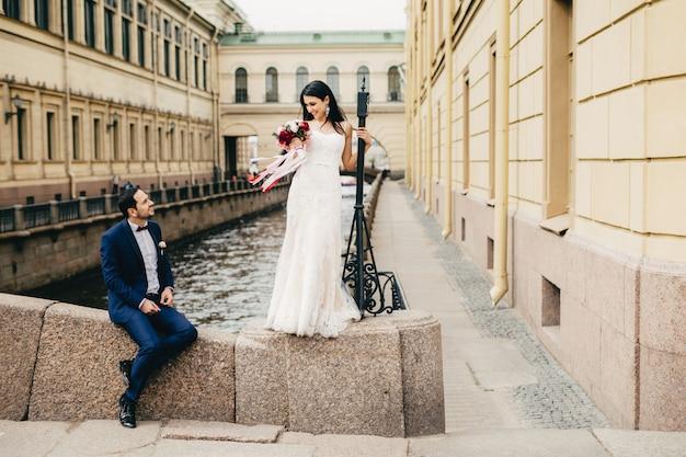 Noivo bonito senta-se na ponte olha para sua linda noiva que se levanta, diz elogios a ela