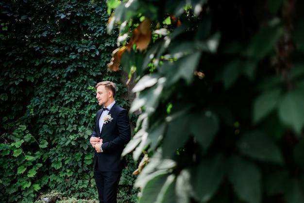 Noivo bonito terno preto e rosa branca boutonniere no jardim