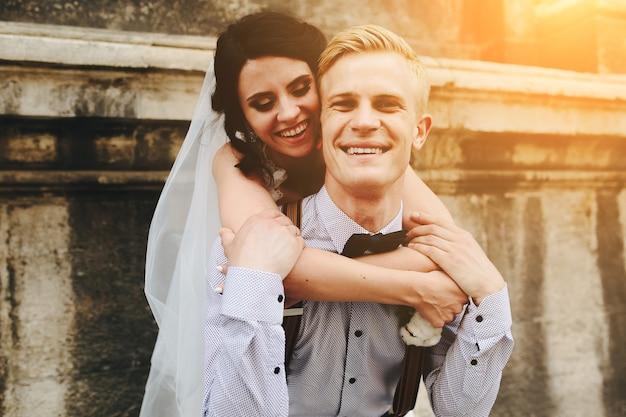 Noivo carrega a noiva nas costas, ao ar livre