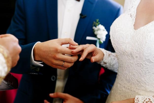 Noivo coloca a aliança no dedo da noiva enquanto eles estão diante de um padre