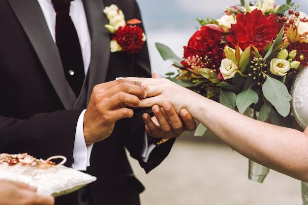 Noivo coloca aliança no dedo da noiva