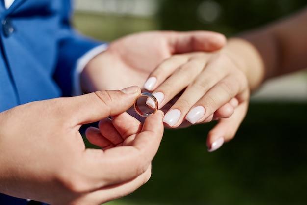Noivo coloca o anel no dedo da noiva no casamento