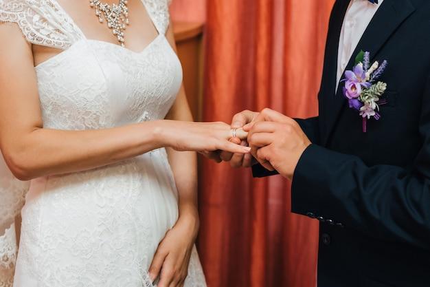 Noivo coloca um anel de casamento de ouro no dedo da noiva