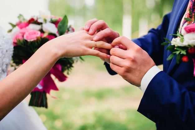 Noivo coloca uma aliança no dedo da noiva