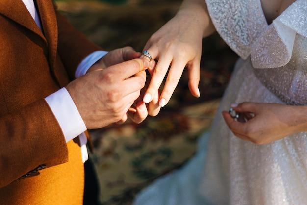 Noivo colocando a aliança no dedo da noiva, cerimônia de casamento