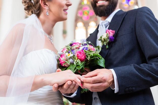Noivo colocando o anel no dedo da noiva no casamento