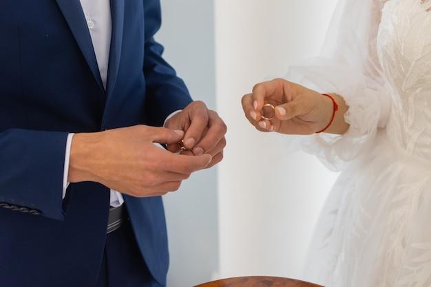 Noivo colocando uma aliança no dedo da noiva.