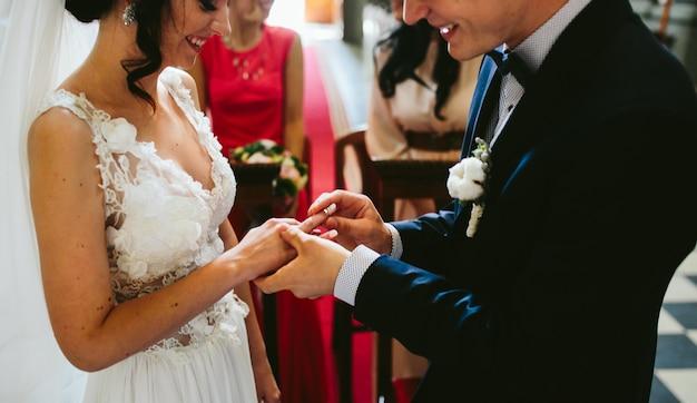 Noivo colocar o anel no dedo da noiva