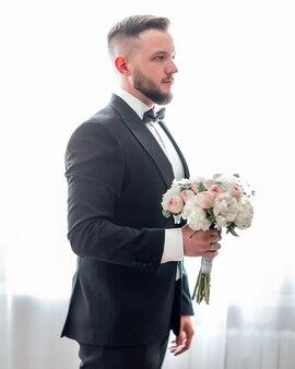 Noivo com buquê de casamento esperando por sua noiva