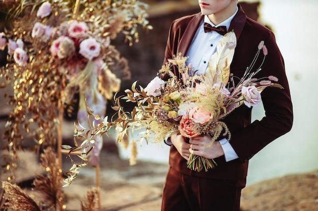 Noivo com um lindo buquê da noiva perto da decoração do casamento em uma cerimônia em um penhasco de rocha perto da água ao pôr do sol.