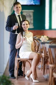 Noivo com uma taça de champanhe e a noiva com um buquê de rosas no café
