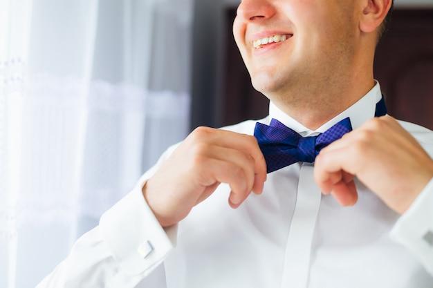Noivo corrige gravata azul. sorriso. fechar-se. metade inferior do rosto