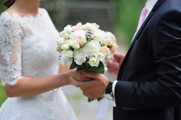Noivo dá a noiva close-up lindo buquê de casamento. para passear no parque.