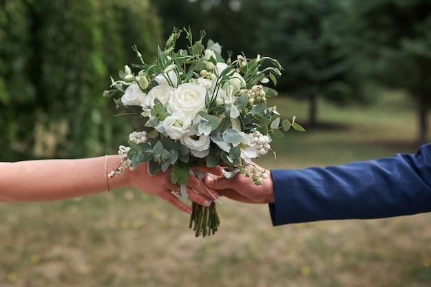 Noivo dá a noiva um lindo bouquet de noiva.