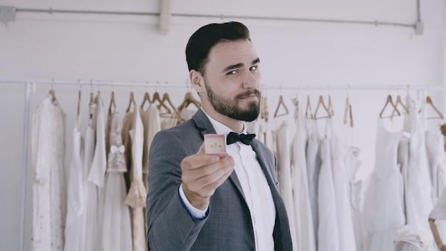 Noivo dando o anel de diamante do casamento para a câmera.