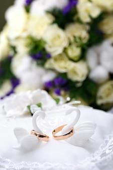Noivo de anéis de casamento de ouro no travesseiro decorativo.
