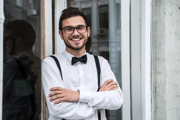 Noivo de camisa branca sorrindo pela janela. em antecipação à noiva.