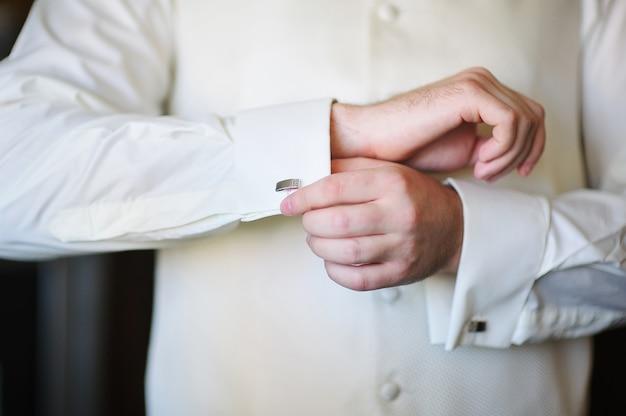 Noivo de manhã no dia do casamento, abotoando as mãos algemas