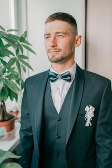 Noivo de terno e gravata borboleta retrato interior
