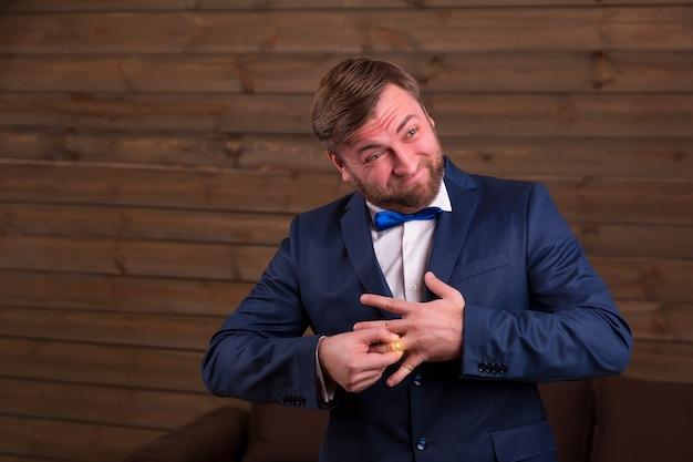 Noivo de terno e gravata borboleta tentando colocar uma aliança no dedo em um quarto de madeira