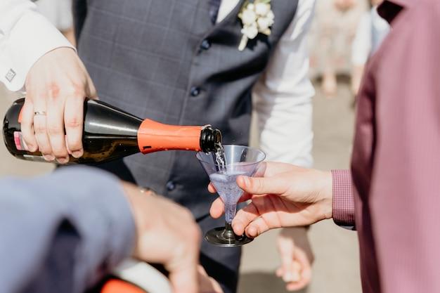 Noivo derrama champanhe em um copo de plástico para close-up de convidados.