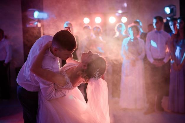 Noivo dobra a noiva enquanto dançam na fumaça na primeira vez