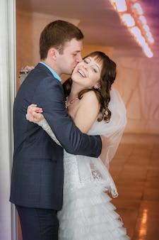 Noivo e a noiva com um buquê de casamento estão perto de uma coluna branca