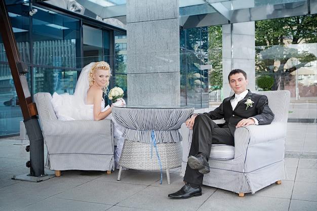 Noivo e a noiva com um buquê de rosas no café