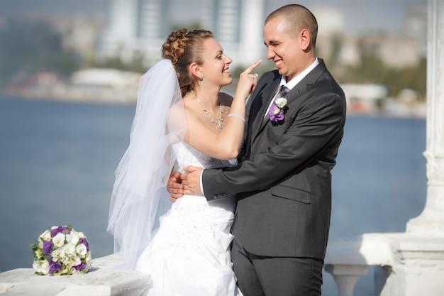 Noivo e a noiva em uma praia no dia do casamento