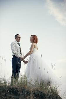 Noivo e noiva à moda delicados elegantes perto do rio ou do lago. casamento, par, apaixonado