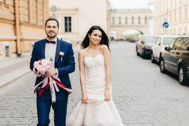 Noivo e noiva caminham juntos, posam para a câmera, têm expressões agradáveis, comemoram o casamento