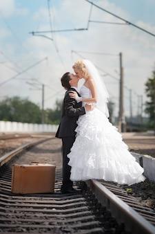 Noivo e noiva com uma mala nos trilhos da estrada de ferro