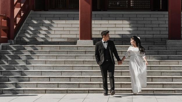 Noivo e noiva de mãos dadas enquanto desce as escadas