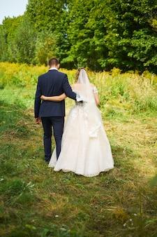 Noivo e noiva em um vestido de noiva, passando o campo em um fundo de céu azul ao pôr do sol
