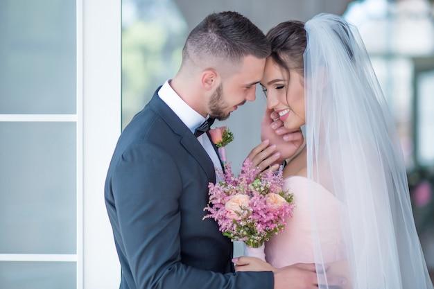Noivo e noiva em um vestido rosa abraçam-se com o amor de pé em um quarto
