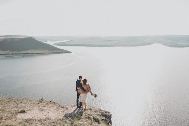 Noivo e noiva em vestido de noiva em um penhasco em frente a um grande reservatório em ilhas distantes