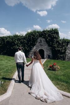 Noivo e noiva estão de mãos dadas e caminhando para uma porta em um muro de pedra no dia ensolarado